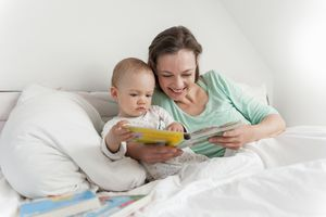 Mother and baby in bed reading picture book