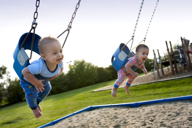 12 Month Old Fraternal Boys Swing Together in Pajamas at a Park