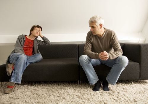 teenage boy rolling his eyes and sitting on couch with father