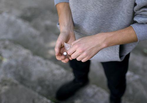 Young man taking narcotic pills