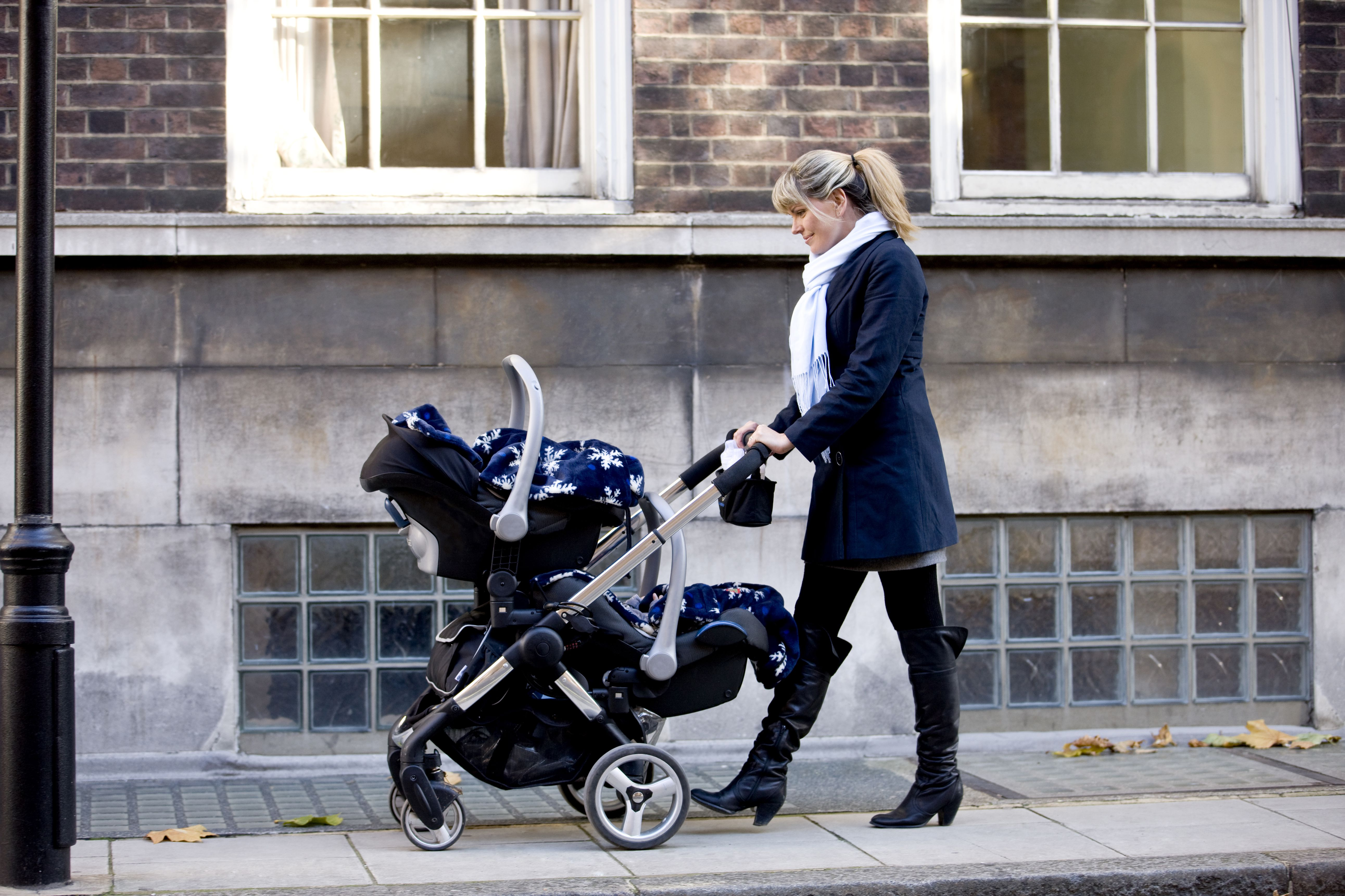Woman pushing a double stroller on a street