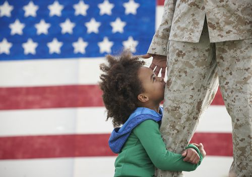 Girl hugging leg of man in Army uniform with U.S. flag in background