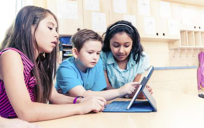 Two girls and one boy using tablet in classroom