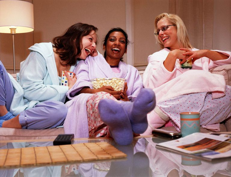 women enjoying a girls night in laughing on couch