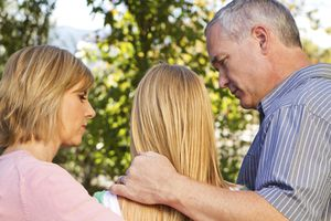 mother and father with their arms around teenage daughter