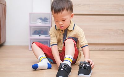 little boy putting on shoes