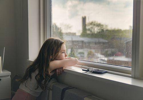 Sad tween girl in quarantine, looking out her bedroom window