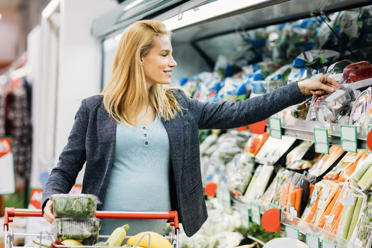 Pregnant Woman Shopping in Supermarket. Choosing vegetable from rack and putting it in shopping chart