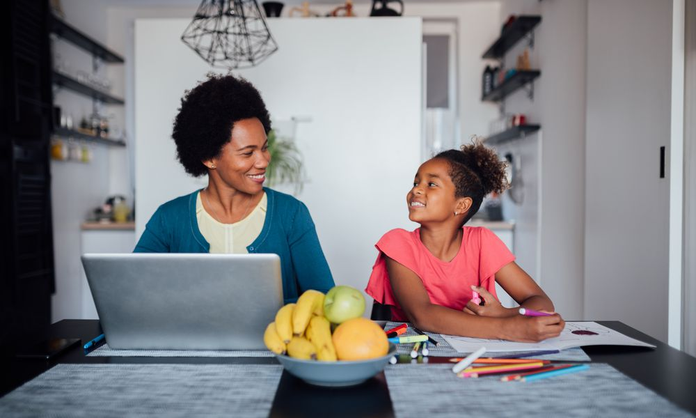 A happy African American family, mature mother working from home on her laptop, while her daughter is homeschooling and doing her homework