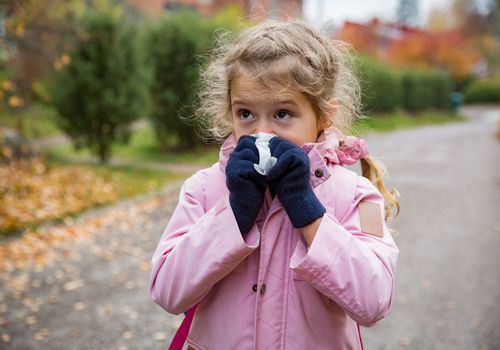 Little girl blowing her nose into a tissue