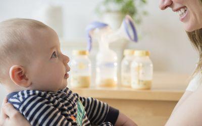 Kaukasische Frau mit Baby-Sohn in der Nähe von Flaschen von Muttermilch