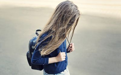 young girl with hair in her face walking outside wearing a backpack