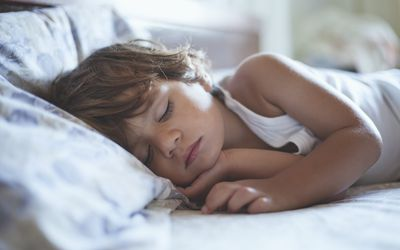 Young child sleeping in bed.