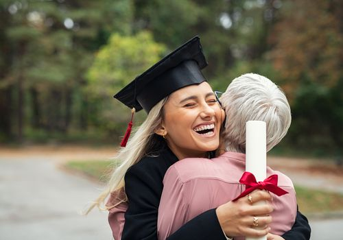 high school graduate hugging mom with diploma