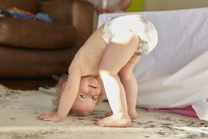 Cute toddler standing on head and smiling