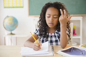 Mixed race student counting on fingers in classroom