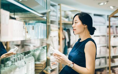Beautiful pregnant woman shopping for beauty products in shopping mall