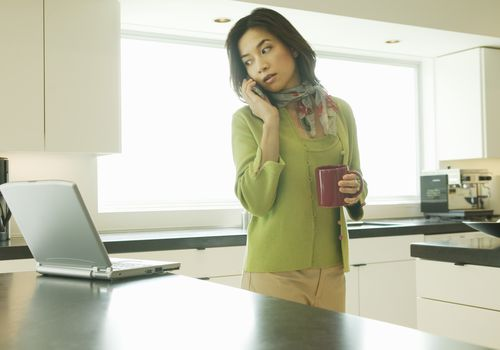 Woman on phone looking at her laptop