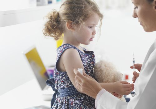 Doctor giving toddler girl a shot