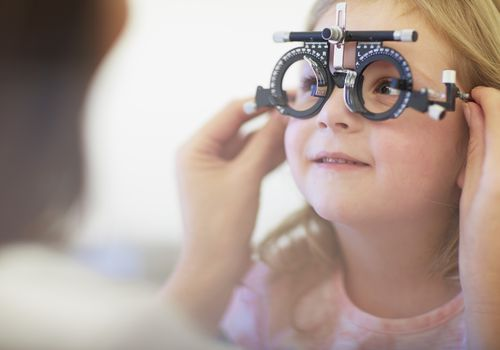 Eye doctor examining young girl's vision