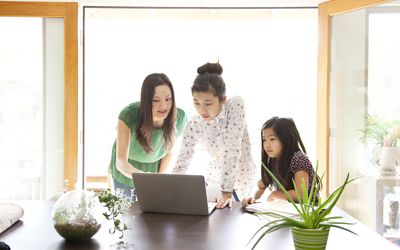 Mother looking over daughter's shoulder at laptop