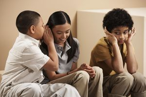 Three children (7-10), boy whispering to girl