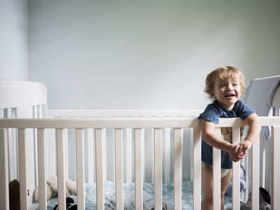 toddler standing and smiling in crib
