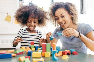 A mom and daughter playing with blocks