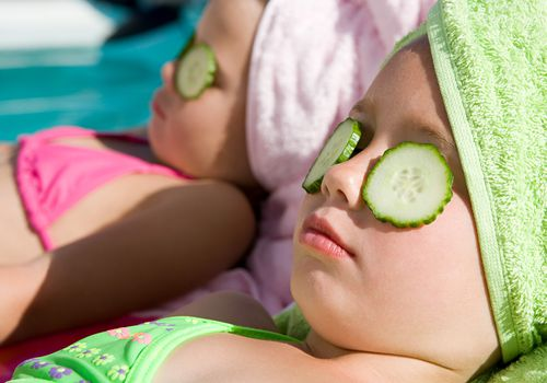 Young girls with cucumber slices on their eyes