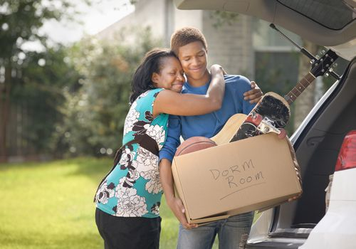 "Mother hugging son who's holding a cardboard box labeled ""dorm room"""