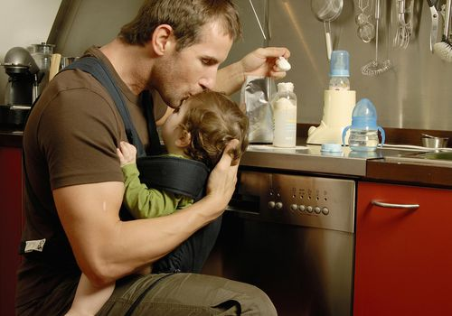 Father carrying baby son while preparing his bottle in the kitchen