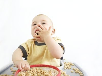 Baby boy sitting in high chair eating cereal