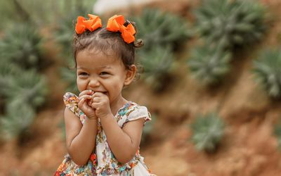 Toddler giggling with orange hairbows outside with plants in the background