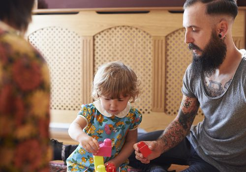 tattooed man helping toddler girl play with blocks