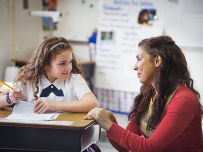 Teacher Kneeling by Desk, Helping a Young Student