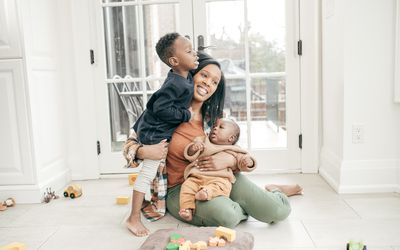 Parent sitting on the floor holding a baby and hugging a toddler