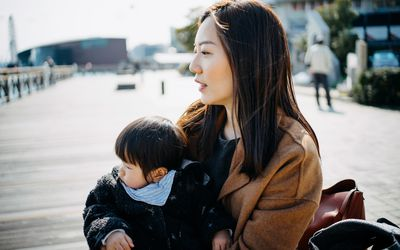 Young Asian single mother embracing cute little daughter on lap, they are sitting outdoor by the pier in deep thought