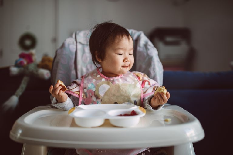 Lovely little baby enjoying breakfast by herself