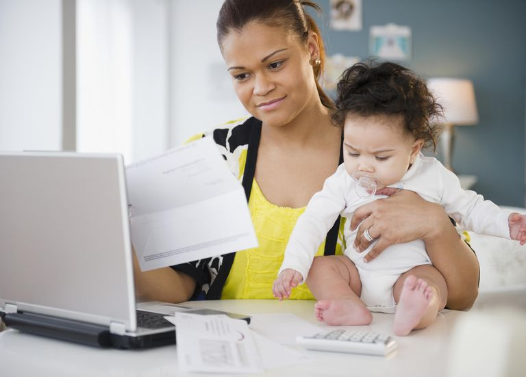 Mixed race mother holding baby and paying bills