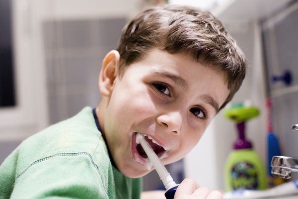little boy using an electric toothbrush