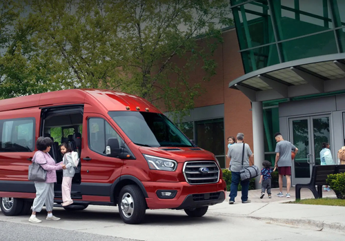 A red Ford Transit Van, with parents and kids walking into a gymnasium