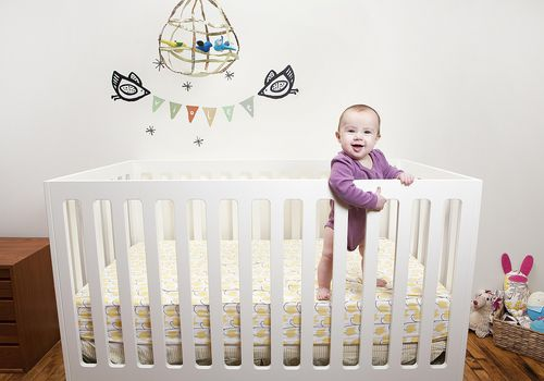 A happy baby in a crib
