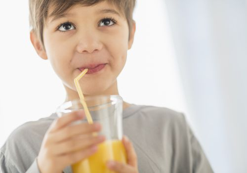 young boy drinking juice with straw