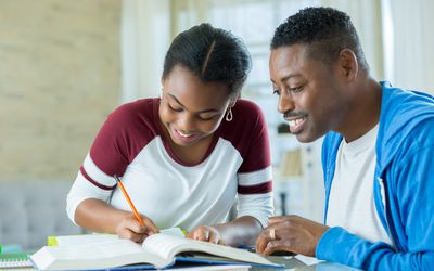 Confident dad helps daughter with homework