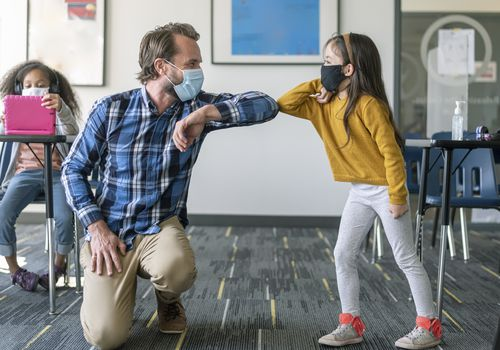 Masked teacher and student greet with elbow bump