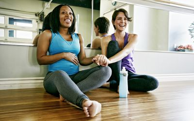 Two women sit on the floor in a prenatal yoga class