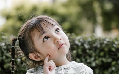 Little girl outside with pigtails looking up and thinking.