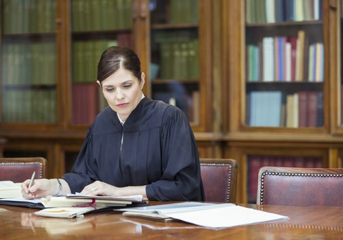 Female judge in her chambers writing at table