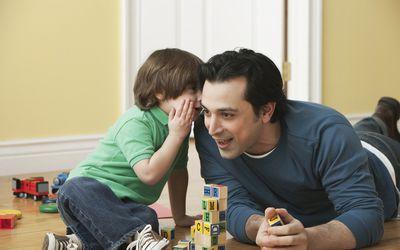 A little boy whispering in his dad's ear