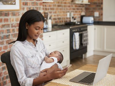 woman holding newborn with laptop and cell